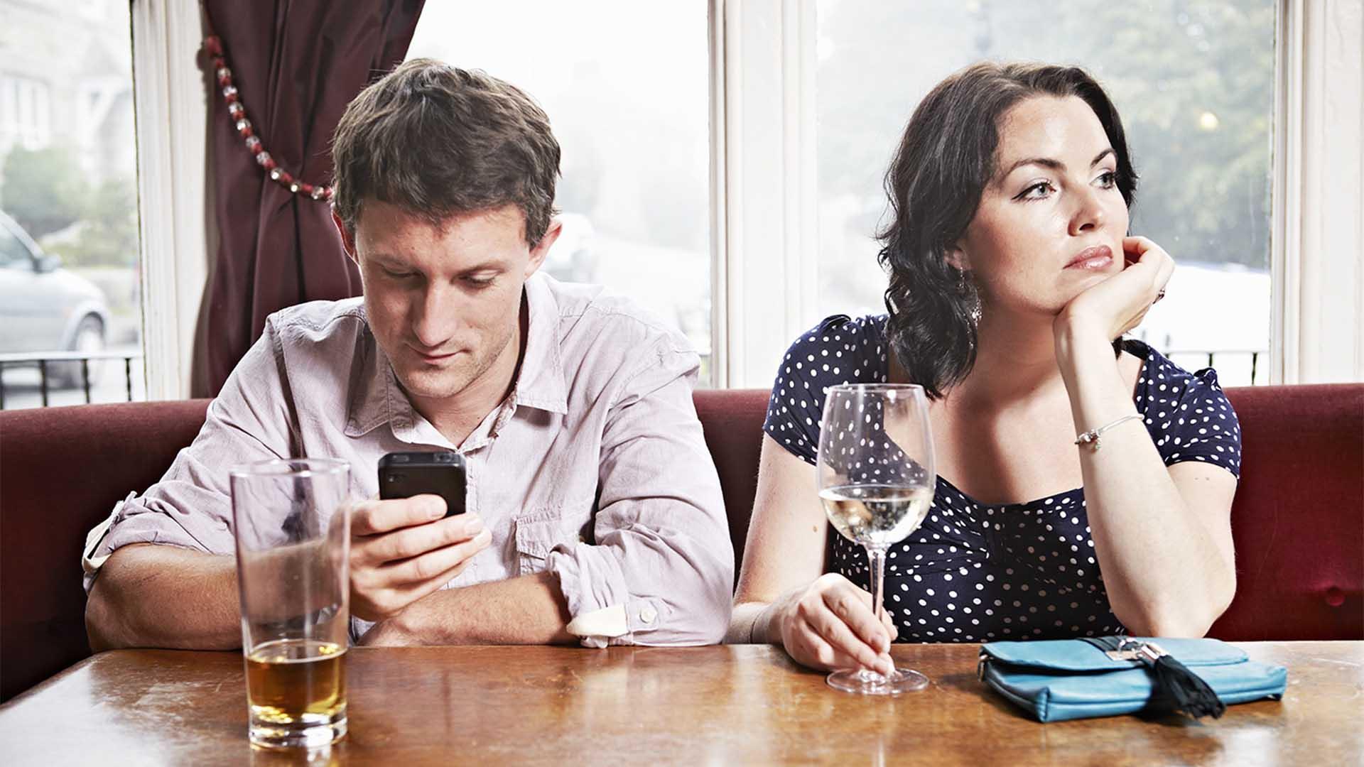 Мужчина и женщина сидят в телефонах